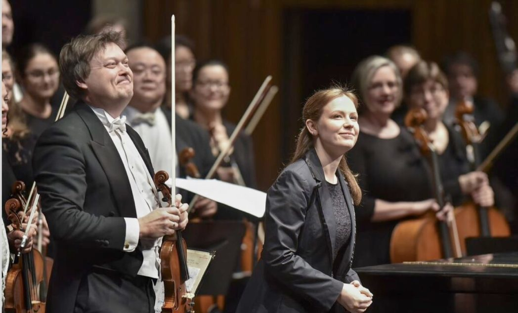 Man and woman with orchestra behind them appreciate audiences applause