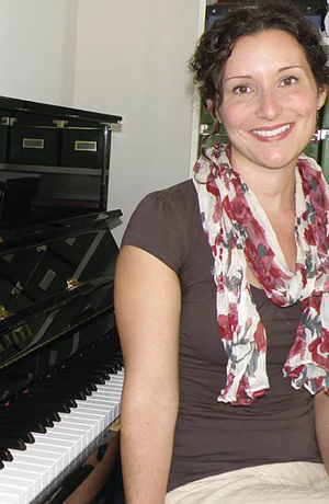 Erin Parkes sitting in front of a piano smiling
