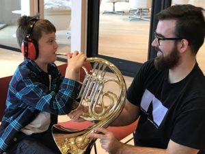 Child with earmuffs trying a horn at a Music Circle event
