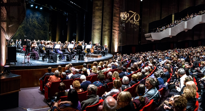 Orchestra on stage with a full audience
