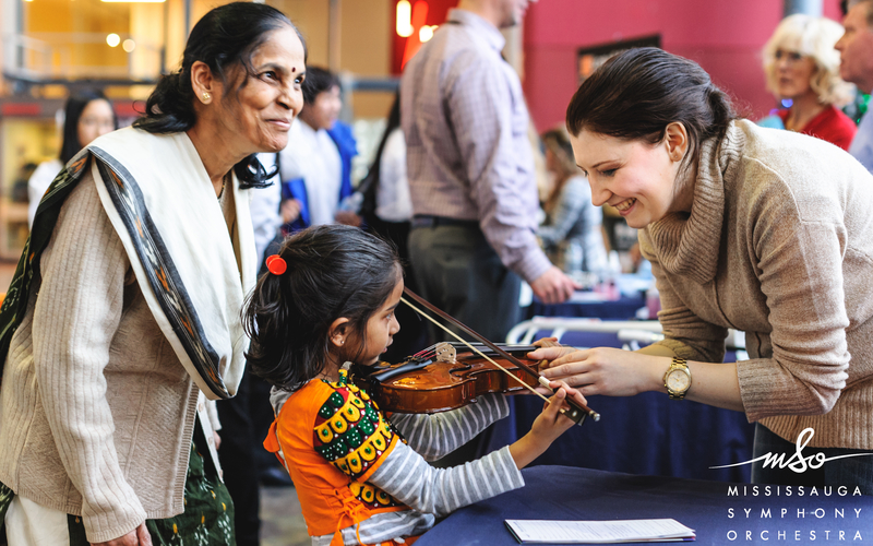Woman teaching child to play the violin with mother watching and smiling